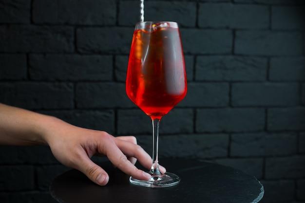De barman serveert een zoete smakelijke cranberrycocktail in een elegant glas met toevoeging van wodka met natuurlijk sap met amandelsiroop en witte rum. de drank wordt gekoeld geserveerd. goede weekendavond