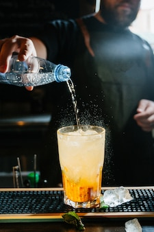 De barman van de hand maakt cocktail. cocktail heeft sinaasappel- en muntblaadjes.