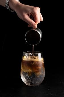 De barman van het meisje bereidt een cocktail voor en giet koffie in een espresso-tonicum.