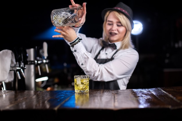 De barman van het meisje formuleert een cocktail op het bierhuis