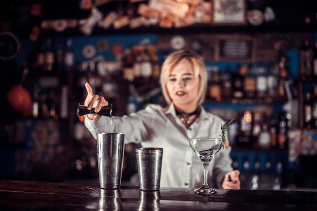 De barman van het meisje maakt een cocktail achter de bar