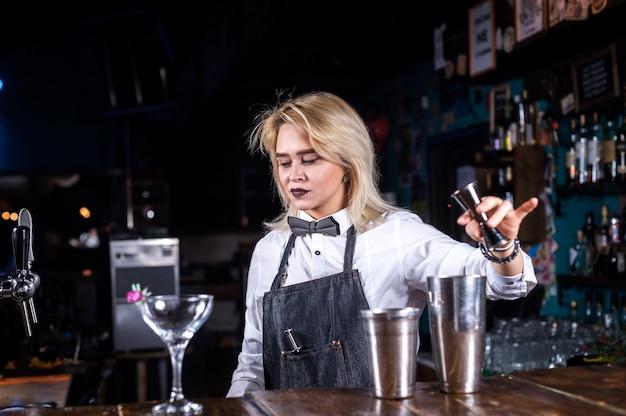 De barman van het meisje maakt een cocktail in de bierhal Premium Foto