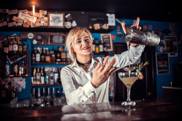 De barman van het meisje maakt een cocktail in de bierhal