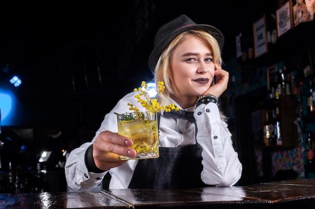 De barman van het meisje maakt een cocktail in de brasserie