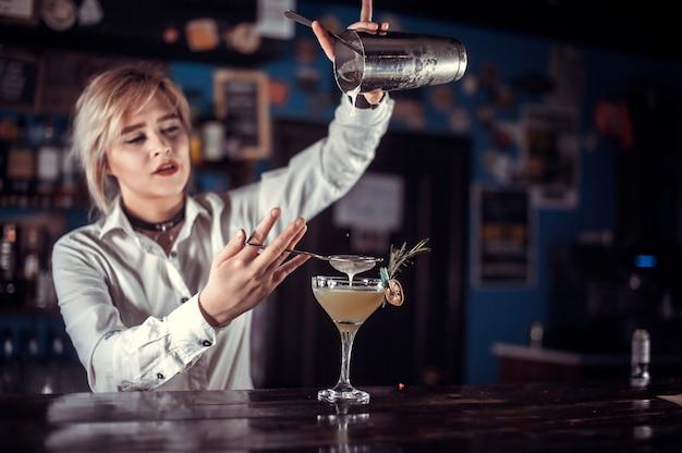 De barman van het meisje maakt een cocktail in de gelagkamer