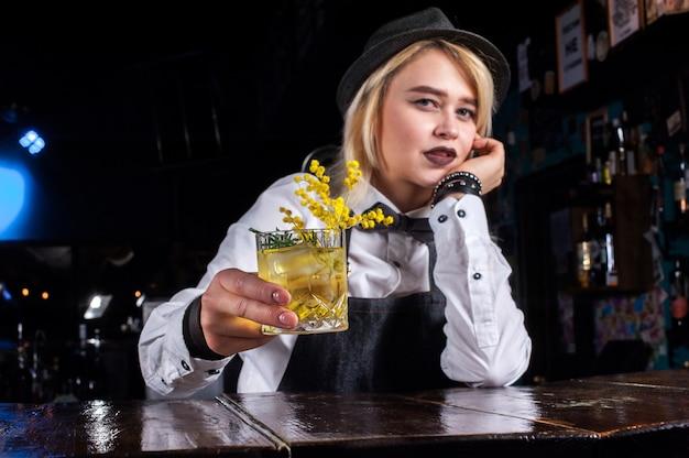 De barman van het meisje maakt een cocktail in de pothouse