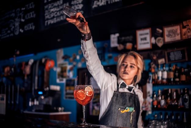 De barman van het meisje maakt een cocktail in de salon
