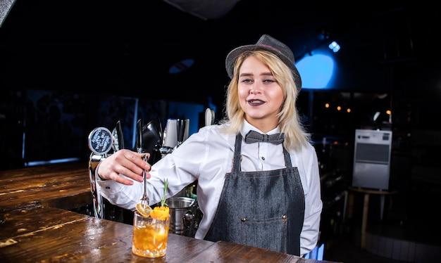 De barman van het meisje maakt een cocktail in het bierhuis
