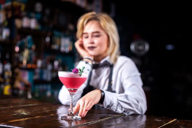 De barman van het meisje maakt een cocktail in het café