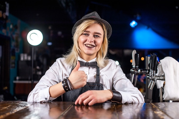De barman van het meisje maakt een cocktail in het portierhuis