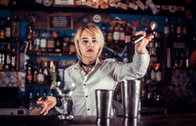 De barman van het meisje maakt een cocktail in het portiershuis