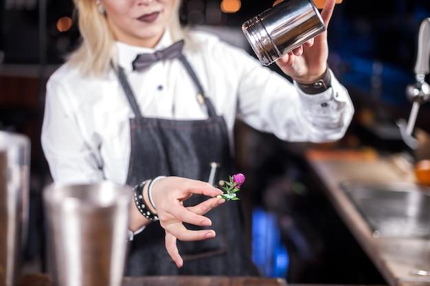De barman van het meisje maakt een cocktail op het café