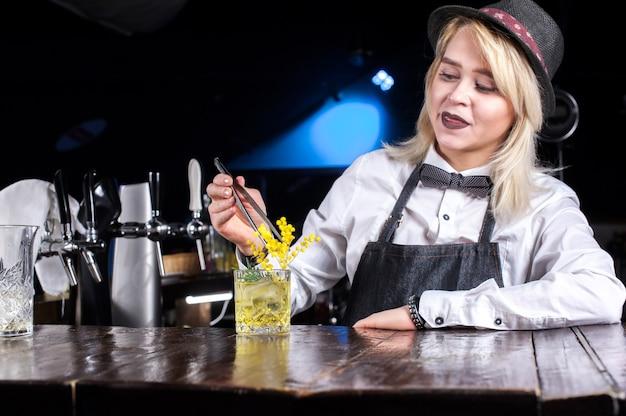 De barman van het meisje maakt een cocktail op het portierhuis