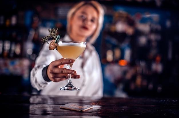 De barman van het meisje maakt een cocktail op het portiershuis