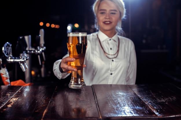 De barman van het meisje mengt een cocktail bij het bierhuis