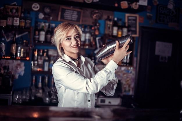 De barman van het meisje mengt een cocktail in de bierhal