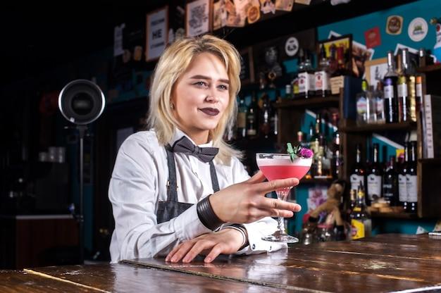 De barman van het meisje mengt een cocktail in de gelagkamer