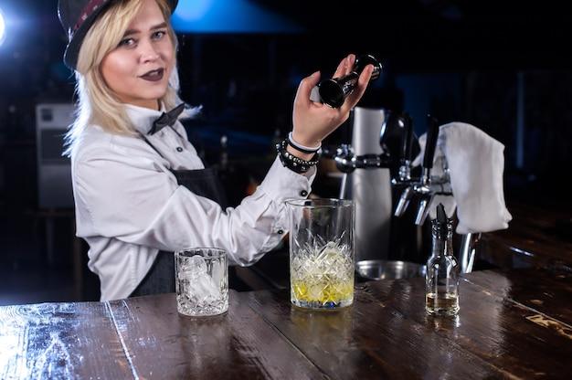 De barman van het meisje mengt een cocktail in de salon