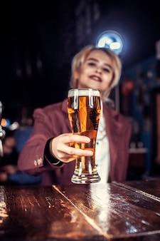 De barman van het meisje mengt een cocktail in het bierhuis