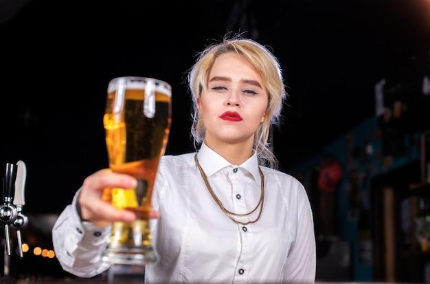 De barman van het meisje mengt een cocktail in het café