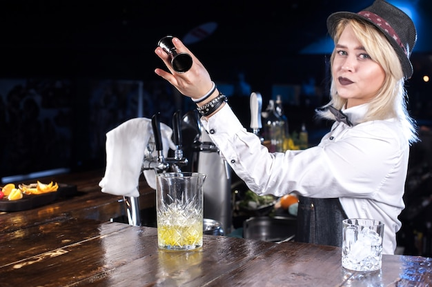 De barman van het meisje mengt een cocktail in het portierhuis