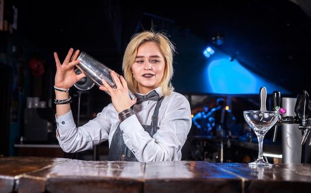 De barman van het meisje mengt een cocktail op het openbare huis