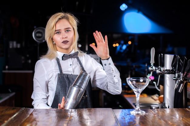 De barman van het meisje mixt een cocktail in de brasserie