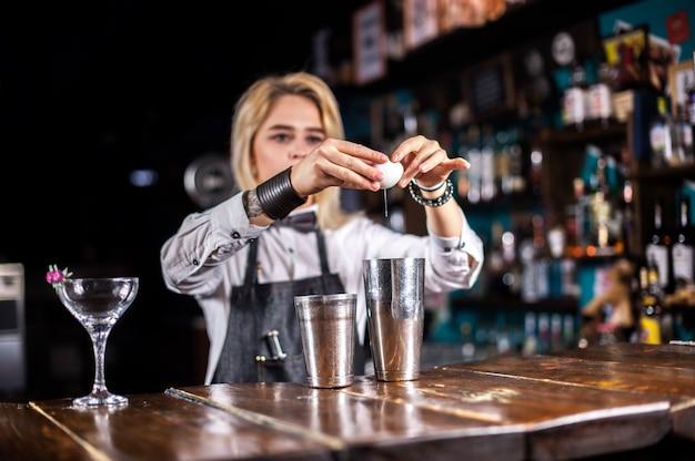 De barman van het meisje verzint een cocktail in de gelagkamer
