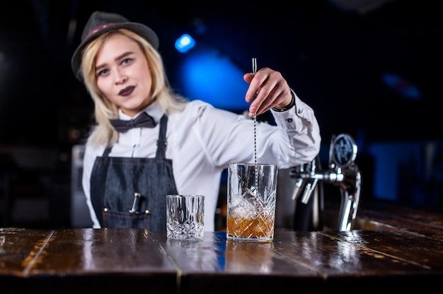 De barman van het meisje verzint een cocktail in de pothouse