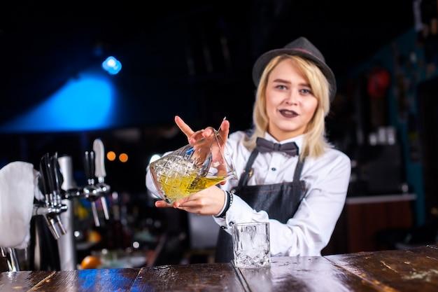 De barman van het meisje verzint een cocktail in het bierhuis