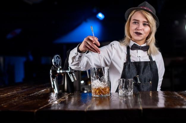 De barman van het meisje verzint een cocktail in het portiershuis