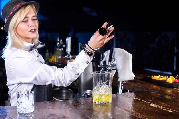 De barmeisje van het meisje formuleert een cocktail op het bierhuis