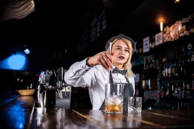 De barmeisje van het meisje maakt een cocktail in het portiershuis