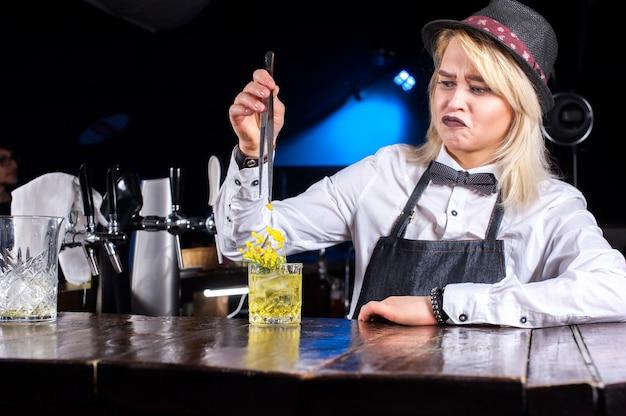 De barmeisje van het meisje maakt een cocktail op de bierhal