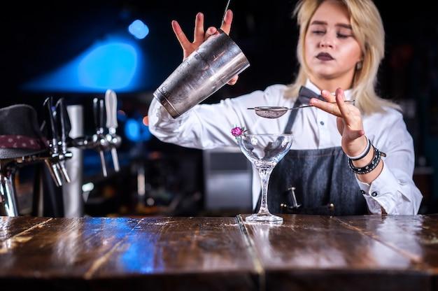 De barmeisje van het meisje mengt een cocktail in het bierhuis