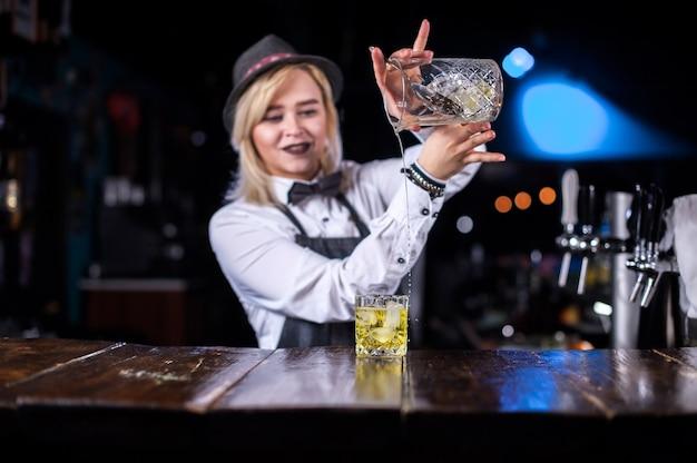 De barmeisje van het meisje verzint een cocktail in de pothouse