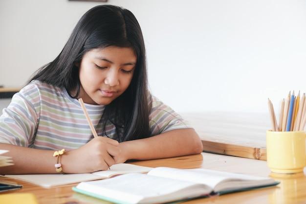 De basisschoolleerling is zelfstudie en maakt thuis huiswerk. onderwijs en afstandsonderwijs voor kinderen. thuisonderwijs tijdens quarantaine.