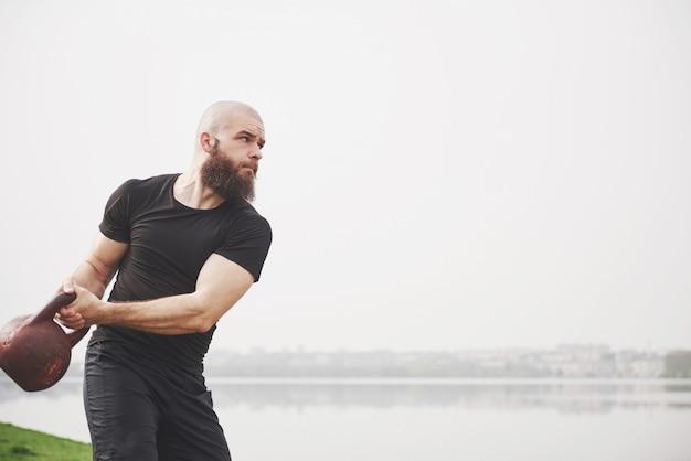 De bebaarde jonge man houdt zich bezig met buitensporten