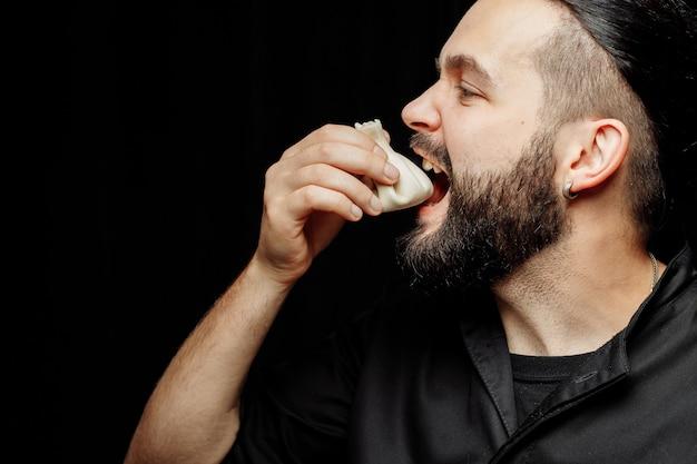 De bebaarde man eet emotioneel khinkali. het nationale georgische gerecht khinkali. concept reclame foto van khinkali.