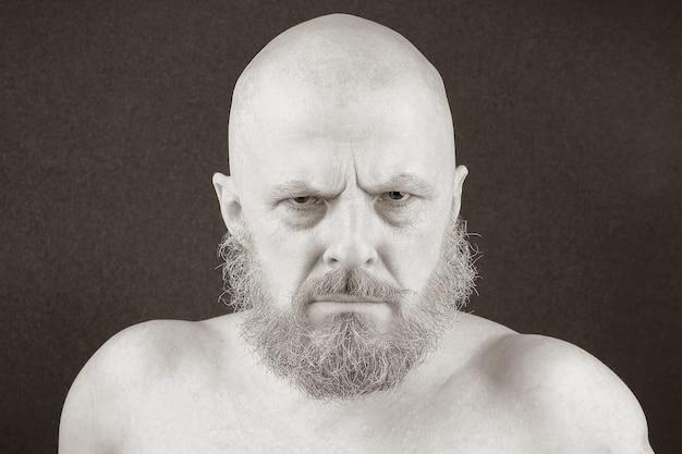 De bebaarde man met een agressieve blik kijkt negatief vooruit. de ernst en agressie van de blik