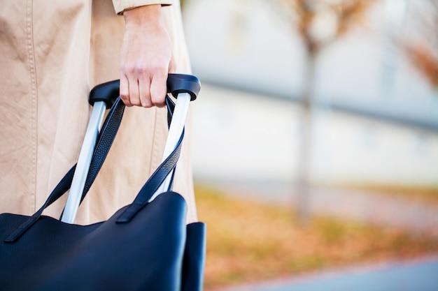 De bebouwde toeristenvrouw van de beeldreiziger kruiste benen in de zomer vrijetijdskleding met koffer op weg in stad openlucht. meisje dat naar het buitenland reist om op weekenduitje te reizen. toerisme reis levensstijl