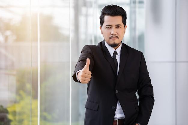 De bedrijfs mens die duimen toont ondertekent omhoog in bureau