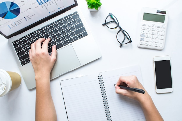 De bedrijfs vrouw neemt nota's en gebruikt calculators en laptops op een witte lijst. bovenaanzicht.