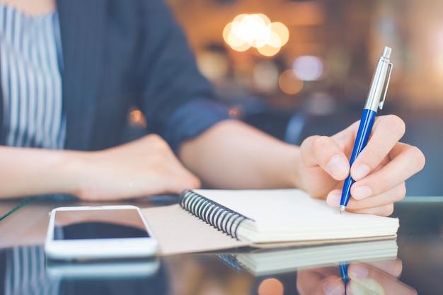 De bedrijfs vrouw neemt nota's over een blocnote met een pen in het bureau.
