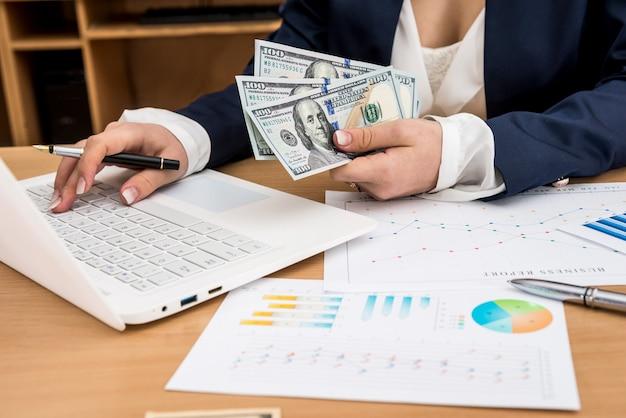 De bedrijfsarbeider houdt de dollars van de vs in hand met laptop en bedrijfsgrafiek