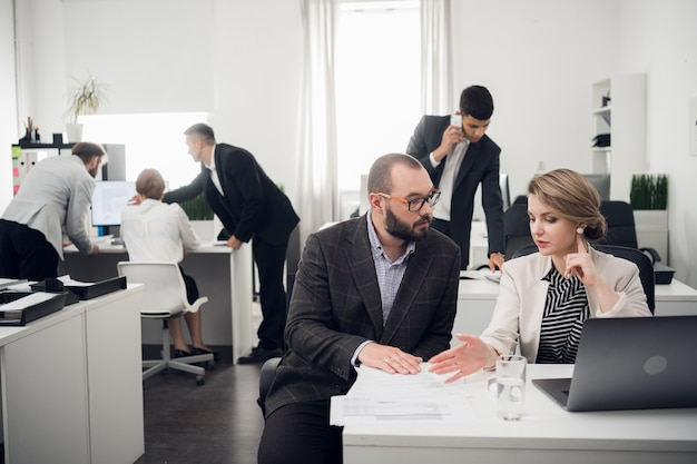 De bedrijfscoach instrueert stagiaires in een ruim kantoor. opleiding van nieuwkomers, stages bij een groot bedrijf