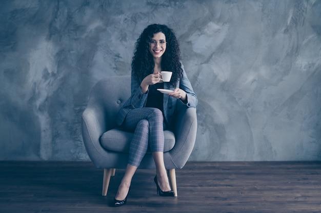 De bedrijfsdame zit in stoel die hete espresso drinkt die over grijze muurachtergrond wordt geïsoleerd