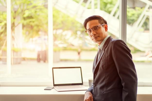 De bedrijfsmens die van azië met laptop werken terwijl het zitten van koffiewinkel concept jonge bedrijfsmensen