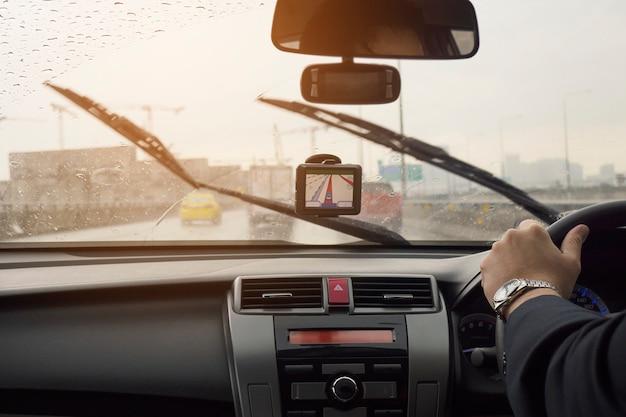 De bedrijfsmens drijft een auto in regenende dag met bewegende wisserbladen