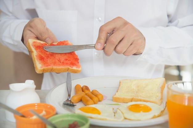 De bedrijfsmens eet het amerikaanse die ontbijt in een hotel wordt geplaatst